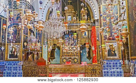 JERUSALEM ISRAEL - FEBRUARY 16 2016: The prayer hall of St James Cathedral with the beautiful altar medieval icons and the numerous oil lamps on February 16 in Jerusalem.