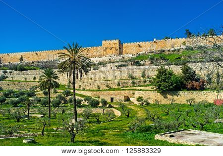 The view on the high ramparts and walled Golden Gate with the Muslim Cemetery in front of it from the Kidron Valley Jerusalem Israel.