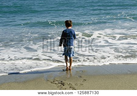 Boy walks toward the waves along the shore