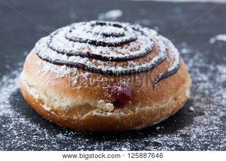 donut with chocolate and marmalade on a black background