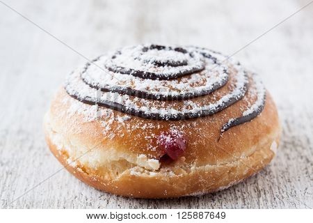 donut with chocolate and marmalade on a white wooden background