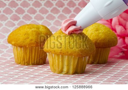 A Cupcake Having Icing Added To It