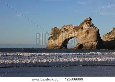 Unique rock formation at Wharariki Beach. Island with big hole. Beautiful scenery at the west coast of the South Island.