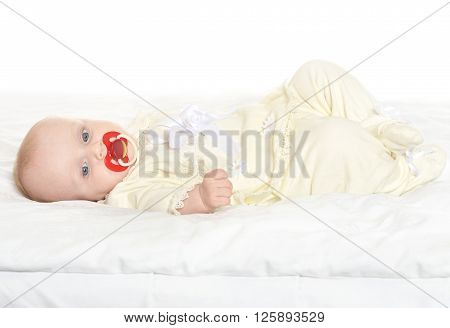Adorable baby girl on blanket with nipple on a white background