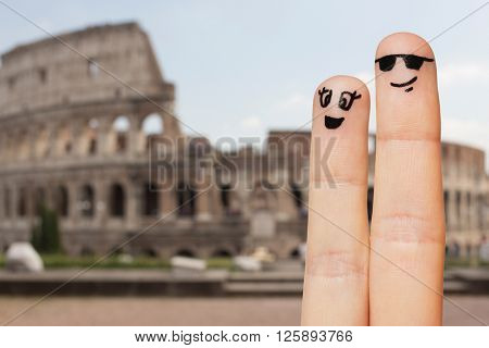family, couple, travel, tourism and body parts concept - close up of two fingers with smiley faces over coliseum in rome background