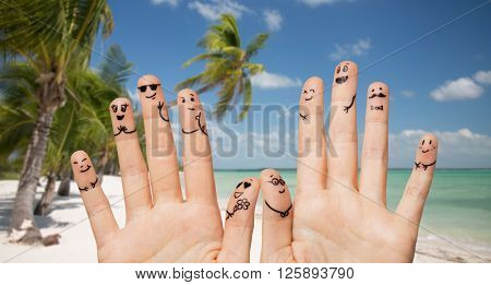 gesture, family, wedding, people and body parts concept - close up of two hands showing fingers with smiley faces over exotic tropical beach with palm trees background