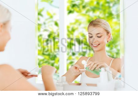 beauty, skin care and people concept - smiling young woman applying lotion to cotton disc for washing her face at bathroom over green natural background