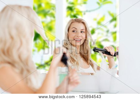 beauty, hairstyle, morning and people concept - smiling young woman with styling iron straightening her hair and looking to mirror at home bathroom over green natural background