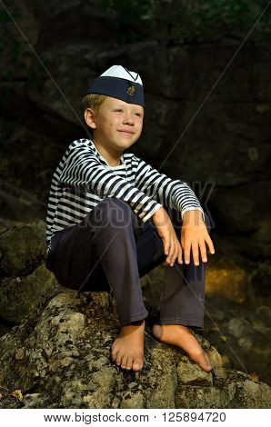 boy in a frock and garrison cap sitting on the stone with barefooted