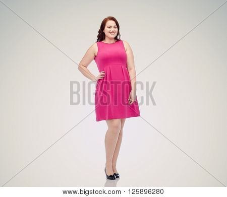 female, gender, portrait and people concept - smiling happy young plus size woman posing in pink dress over gray background
