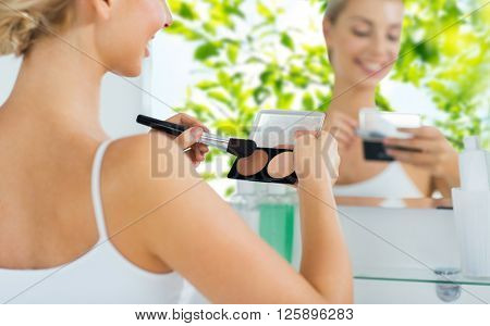 beauty, make up, cosmetics, morning and people concept - close up of happy young woman with makeup brush and contouring highlighting palette at bathroom over green natural background
