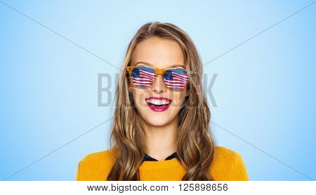 people, patriotism and nationality  concept - happy young woman or teen girl face in sunglasses with american flag over blue background