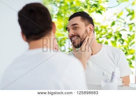 beauty, hygiene and people concept - smiling young man looking to mirror at home bathroom over green natural background