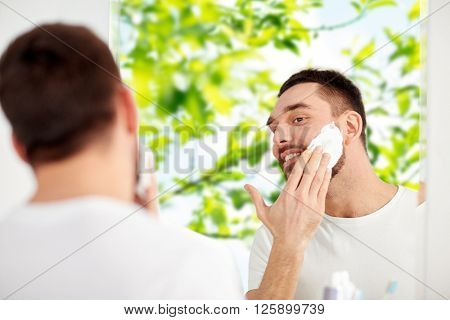 beauty, hygiene, shaving, grooming and people concept - smiling young man looking to mirror and applying shaving foam to face at home bathroom over green natural background