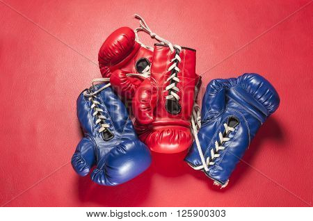 Boxing series : Red and blue boxing gloves on red leather background