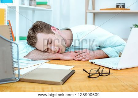 IT company. Young programmer with laptop. Nice office interior. Professional coder sleeping
