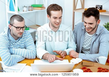 IT company. Young programmers working with laptop with pizza. Nice office interior. Professional coders looking at laptop and smiling