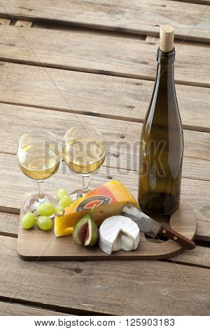 Image Of Wooden Board With Wineglasses Cheese And Fruits