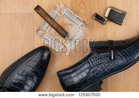 Male still life classic men's shoes and a cigar in an ashtray can use as background