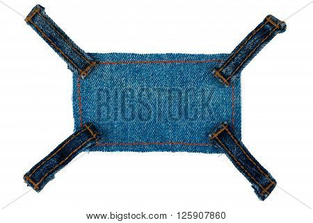 Frame with four straps jeans lies on the dark denim isolated on white background