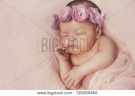 Peaceful sleep of a newborn baby on a pink bed covered with a pink quilt,cute little wreath on his head, sleeping sweetly tucked arms and legs on a pink background