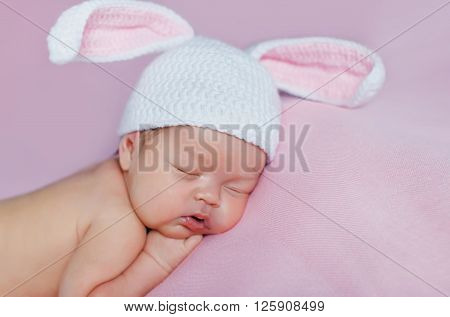 Peaceful sleep of a newborn baby on a pink bed,cute baby in hat with Bunny ears, sleeping sweetly tucked arms and legs on a pink background