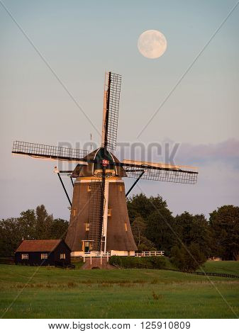 Windmill in the countryside in Holland during sunset under a rising bright full moon.