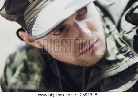 war, army and people concept - close up of young soldier in military uniform