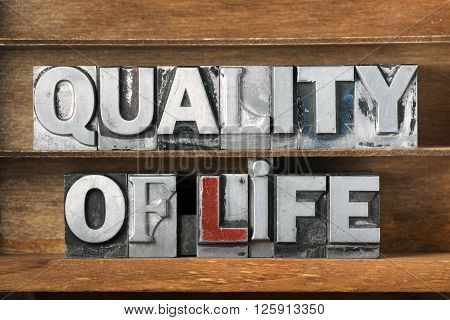 quality of life phrase made from metallic letterpress type on wooden tray