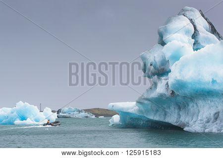 Man on a small boat in Jokulsarlon Glacial Lagoon near Vatnajokull in south coast of Iceland