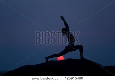 Warrior pose from yoga by woman silhouette with the first light of rising sun