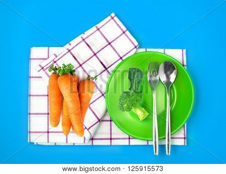 the top view of fresh broccoli and carrots in green dish and towel on vibrant color background healthy food concept