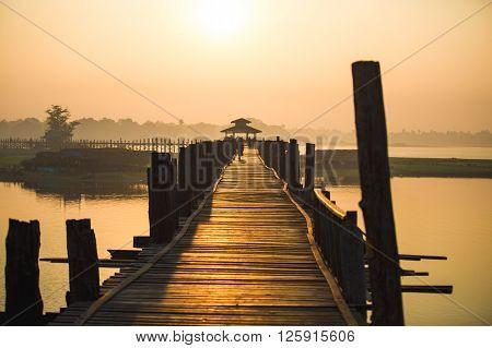 MANDALAY, MYANMAR - January 9, 2015: People walk on U Bein bridge at sunrise