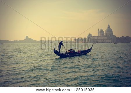 Traditional Gondola on Canal Grande with San Giorgio Maggiore church in the background in at sunset San Marco Venice Italy (Filtered image processed vintage effect)