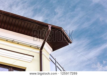 Metal Rain Gutter White Downspout On Corner Of House