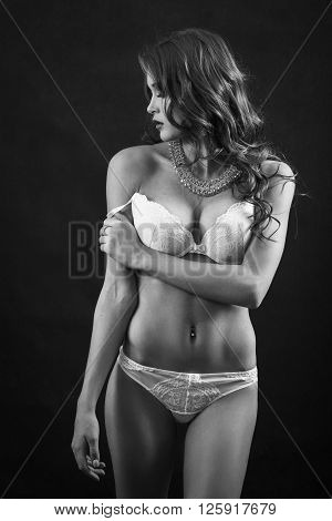 beautiful woman with big breast in white lingerie undressing on black background monochrome image
