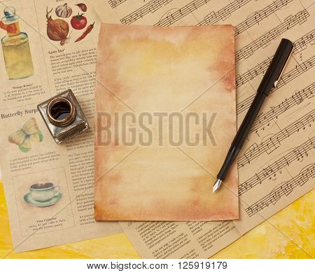 A sheet of aged paper with a dip pen and an ink bottle lying on scraps of old papers sheet music and newspapers (the newspaper is a vintage styled mockup) with copyspace