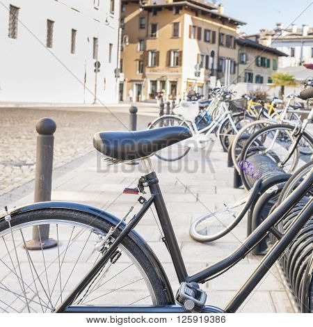 Bicycle parked on a rack in a large city.