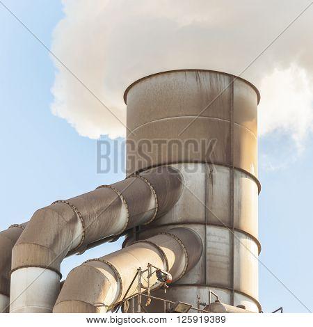 Pollution of old smokestack that emits white smoke.