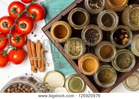 Close photo of spices and herbs small glass jars. Food cuisine ingredients: carry chilly turmeric blue painted wooden board. Cherry tomatoes branch. Food cuisine ingredients photography.