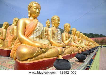 Thousand of Golden Buddha statues with clear sky.