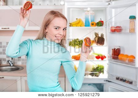 Pretty blonde standing near open fridge full of food. Young woman smiling and having fun with blood orange