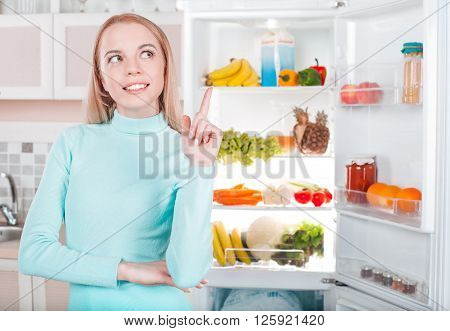 Pretty blonde standing near open fridge full of food. Young woman looking aside, smiling and pointing at fridge