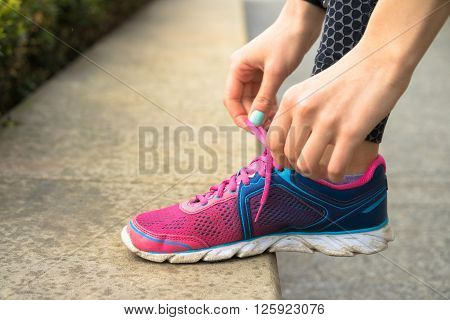 Female hands with manicure tie laces on pink and blue sneakers while jogging in the park