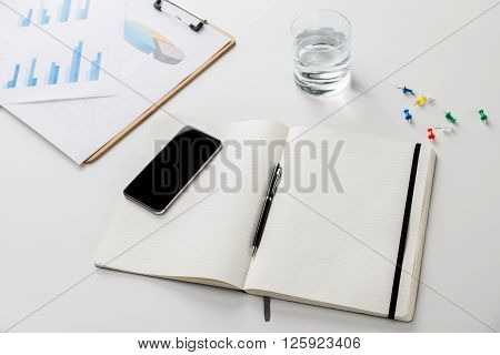 Topview of desk with empty lined copybook; mobile phone and business graphs