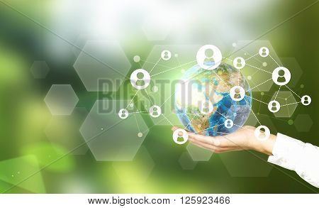 Terrestrial globe with networking system in male palm on abstract green background.