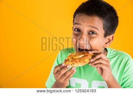 indian boy eating pizza over yellow background