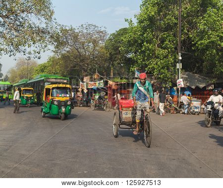 DELHI INDIA - 19TH MARCH 2016: A view of roads and streets in Delhi during the day showing Tuk Tuks rickshaws buses and people.