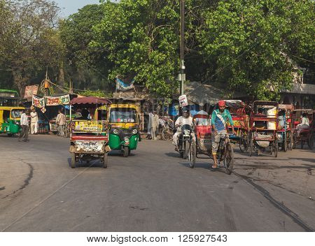DELHI INDIA - 19TH MARCH 2016: A view of roads and streets in Delhi during the day showing Tuk Tuks rickshaws and people.
