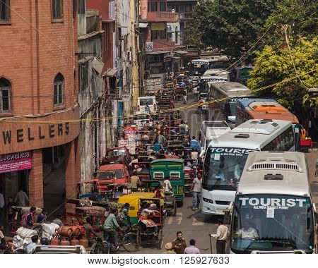 DELHI INDIA - 19TH MARCH 2016: Long queues of traffic in central Delhi during the day. Buses Rickshaws other vehicles and people can be seen.